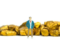 Figure miniature businessman or small people with pile of gold nuggets or gold ore on white background, precious stone or lump of. Golden stone, financial and stock photography