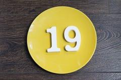Figure nineteen on the yellow plate. Figure nineteen on the yellow plate and brown background stock photo