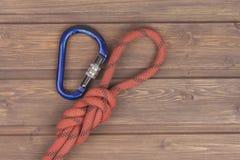 Figure noeud de huit avec le carabiner s'élevant sur le fond en bois Photos stock