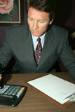 Figure it out. Business man calculates and projects with caution Stock Photography