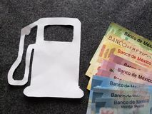 Figure of the petrol pump in white paper and mexican banknotes of different denominations. Price of fuel in Mexico, petrol and diesel for the transport industry stock photo