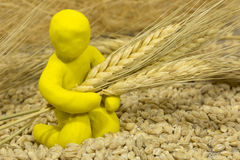 Figure plasticine man sits among the wheat and keeps holding ear Stock Photos