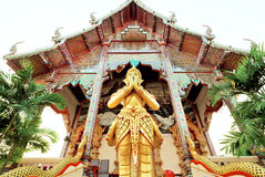 Figure of praying statue standing at door of ancient Buddhist temple structure, Thailand Royalty Free Stock Image