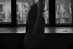 Figure of a pregnant woman on window background. Dark walls in the room. Black and white photo. Stock Images