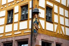 A figure of a saint on a corner of a German house. Stock Photos