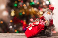 Figure of Santa with a bag of gifts on the boke. Figure of Santa Claus with a bag of gifts on the background bokeh Royalty Free Stock Photo
