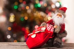 Figure of Santa with a bag of gifts on the boke. Figure of Santa Claus with a bag of gifts on the background bokeh Royalty Free Stock Photography