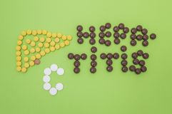 Figure or shape contour of human liver, composed of yellow tablets, and the diagnosis of hepatitis C sign made of yellow and whi. Te pills or tablets on a green stock photo