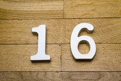 The figure is sixteen on a wooden, parquet floor. The figure is sixteen on a wooden, parquet floor as a background Royalty Free Stock Images