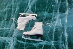 Figure skates at transparent cracked ice surface close up. Winter sport concept. Lake Baikal stock image