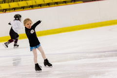 Figure skating. Cute young girl practicing figure skating on indoor ice skating rink Royalty Free Stock Image