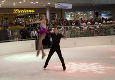 Figure skating performance on holiday Galleria ice center. Excellence pair figure skating perform movements, including complicated lifts on holiday Galleria ice Stock Photo