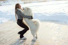 Figure skating woman with dog Samoyed Stock Photo