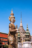 Figure, Spires and Roof against a dark blue sky at Grand Palace, Thailand Stock Photos