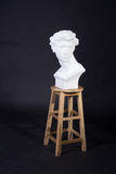 Figure. The statue was placed on a chair man curly hair Stock Image