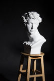 Figure. The statue was placed on a chair man curly hair Stock Photography