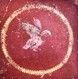 Figure stylisée d'un oiseau sur un fond rouge, fresque romain antique dans un domus de Pompeii photographie stock libre de droits