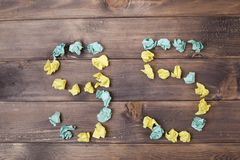 Figure 95 on a table. Crumpled pieces of paper in the form of balls, forms figure 95 on a dark wooden Royalty Free Stock Photos