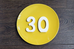 Figure thirty on the yellow plate. Royalty Free Stock Image