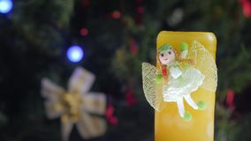 Figure of a toy frog. Is spinning in front of the camera. Christmas tree with Christmas balls on the background. Close-up stock footage