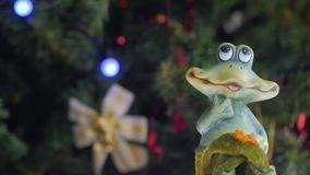 Figure of a toy frog. Is spinning in front of the camera. Christmas tree with Christmas balls on the background. Close-up stock video