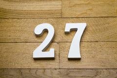 Figure twenty-seven on a wooden, parquet floor. Figure twenty-seven on a wooden, parquet floor as a background Royalty Free Stock Photo