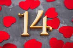 Figure una e quattro e cuori su un fondo grigio Il simbolo del giorno degli amanti Giorno del biglietto di S Concetto 14 febbraio Fotografia Stock Libera da Diritti