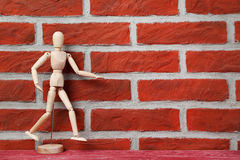 Figure. Wooden figure on a brick wall background Royalty Free Stock Images
