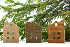 Figure of a wooden house on a background of green fir branches Stock Photos