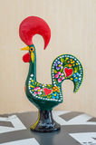 Figure of wooden rooster. Carved in Portugal on a background of wall Stock Photos