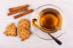 Figured cookies, cinnamon, tea in cup, spoon on saucer on table. Top view. Figured cookies, cinnamon sticks, tea in cup, spoon on saucer on wooden table. Top stock photo