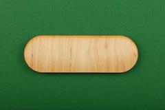 Figured formte Holzschild auf grünem Hintergrund Lizenzfreies Stockfoto