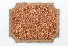 Figured frame of burlap with  buckwheat  grains Royalty Free Stock Photos