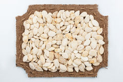 Figured frame of burlap with pumpkin seeds Stock Photo