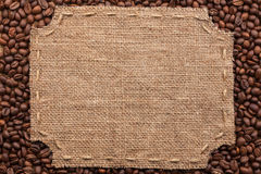 Figured frame with burlap and stitches with  place for your text. Lying on coffee beans as a background Royalty Free Stock Image