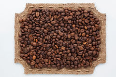 Figured frame made of burlap and coffee beans. Lie on a white background Stock Photos