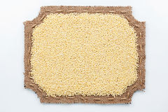 Figured frame made of burlap and  millet  grains Royalty Free Stock Image