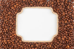 Figured frame  made of rope with  coffee beans  lying on a white Royalty Free Stock Images