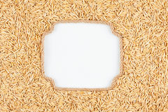 Figured frame made of rope with  oats  grains  lying on a white Stock Photos