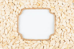 Figured frame made of rope with  pumpkin seeds  lying on a white Royalty Free Stock Photography