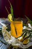 Figured glass of yellow fruit juice with a slice of lemon and gr. Een leaves, standing on crumpled wrapping paper on a wooden table on the background of a red Stock Photos