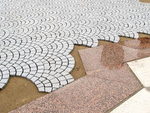 Figured laying of paving slabs and red granite plates on the square.  Stock Images