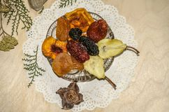Figured napkin with a crystal rosette filled with dried fruits,and small eclairs on plywood. Figured napkin with a crystal rosette filled with dried ts,and small Stock Photos