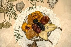 Figured napkin with small eclairs,a crystal rosette with dried fruits lying on plywood. Figured napkin with small eclairs,a crystal rosette with dried ts Stock Images