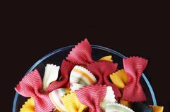 Figured pasta on a black background. Multicolored pasta. Beautiful pasta in the form of a butterfly. Original italian pasta isolated on a black background Royalty Free Stock Photography