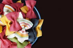 Figured pasta on a black background. Multicolored pasta. Beautiful pasta in the form of a butterfly. Original italian pasta isolated on a black background Stock Image