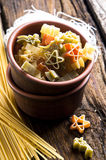 Figured Pasta and noodles. Figured Pasta in bowl and noodles on wooden background stock images