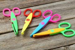 Figured scissors. On grey wooden background Royalty Free Stock Photo