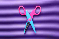 Figured scissors. On the purple background Royalty Free Stock Image