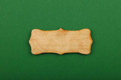 Figured shaped wooden sign on green background. Figured ornately shaped blank wooden sign with copy space in center of green design paper background, title slide Royalty Free Stock Photo